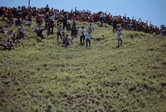 Competitors pursue a Double Gloucester cheese in the annual Cheese Rolling event at Cooper's Hill, Painswick, Gloucestershire, England.